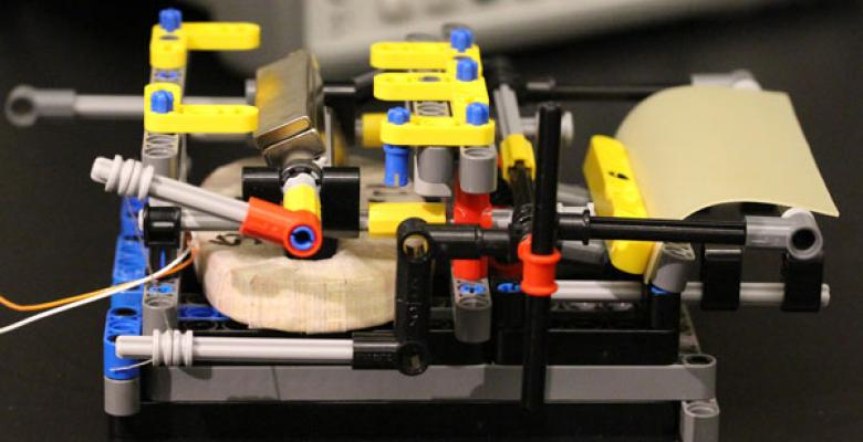An evaporation harvesting device made of Legos, a spore-coated rubber sheet, a coil and a magnet. The device produces electricity when sheet bends and straightens in response to moisture. Image Credit: Xi Chen/Columbia University